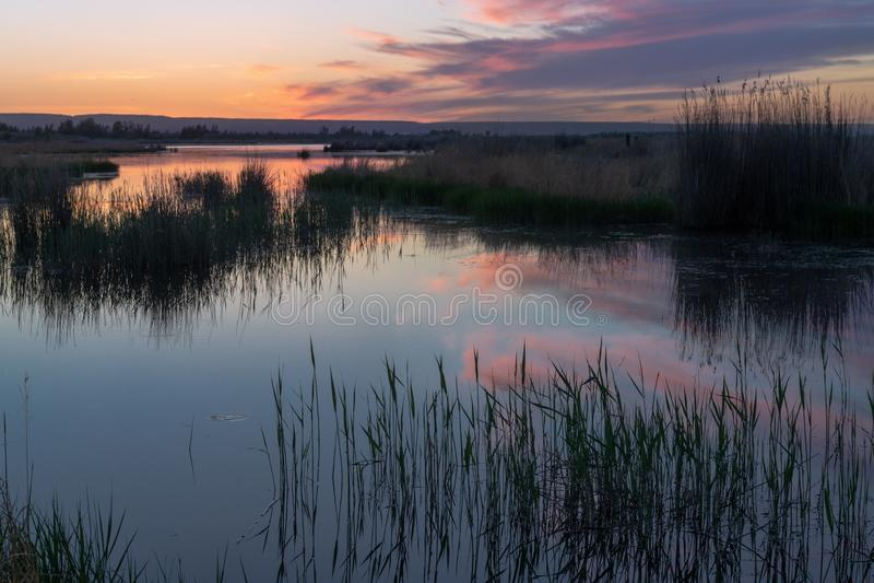 Por do sol bonito com as nuvens roxas no lago imagens de stock royalty free
