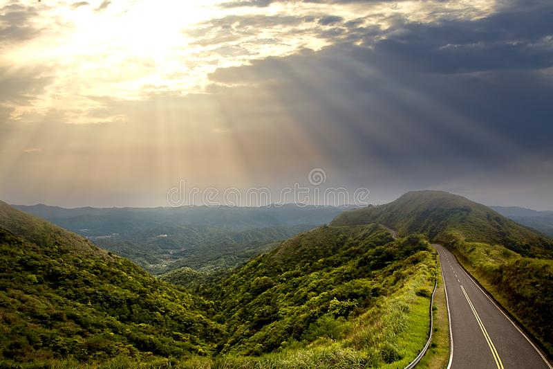 Por do sol bonito com raios do sol sobre os contornos das montanhas e de uma estrada ao longo da parte superior da montanha no fu imagens de stock