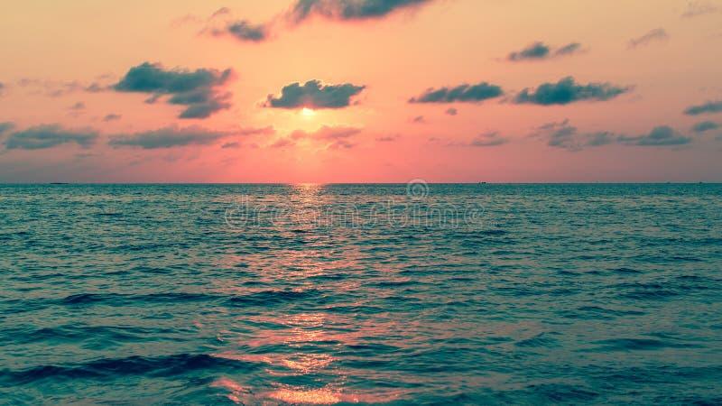 Por do sol bonito com reflexões vermelhas sobre um mar calmo nave imagem de stock