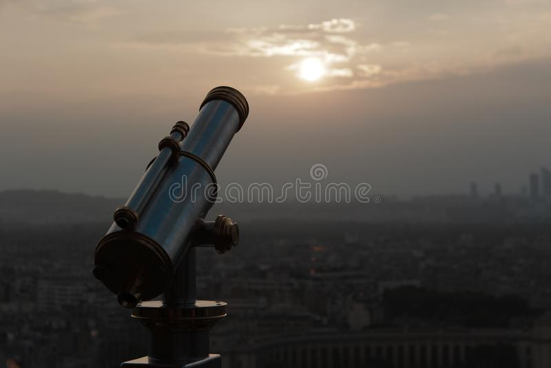 POR DO SOL BONITO COM VISTAS À CIDADE DE PARIS E DE UM GRANDE TELESCÓPIO fotos de stock