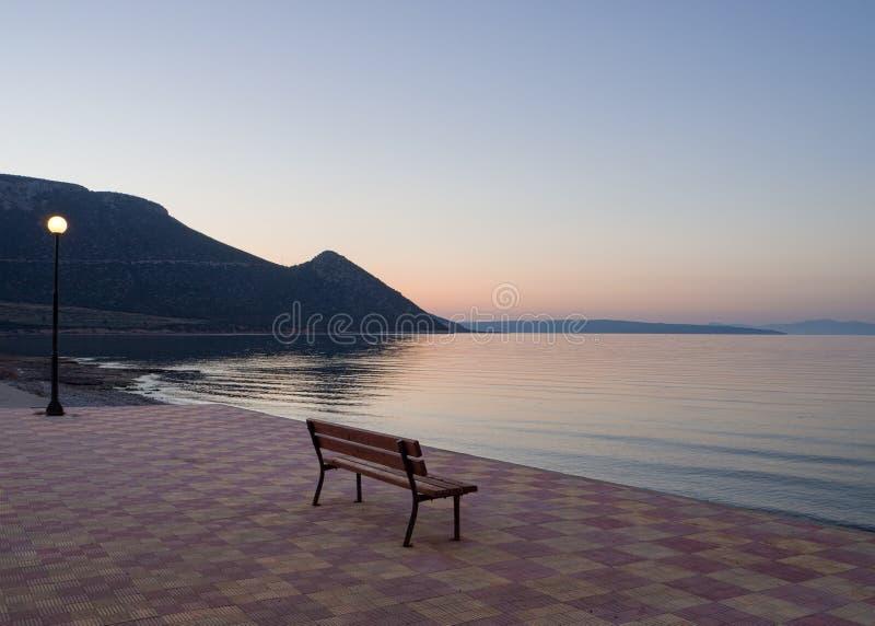Por do sol bonito e banco na frente marítima em Grécia imagens de stock royalty free