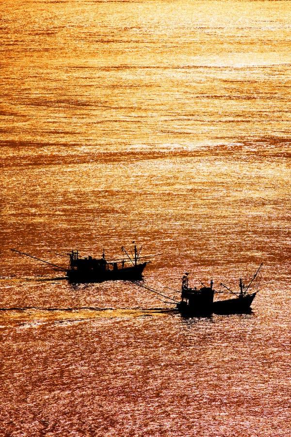 Por do sol bonito e barcos de pesca locais no mar na ilha de Lipe, mar de Andaman, Satun, Tailândia fotografia de stock