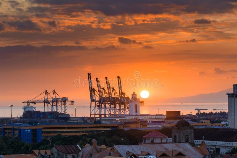 Por do sol bonito e guindastes industriais da carga na baía de Manila imagens de stock royalty free