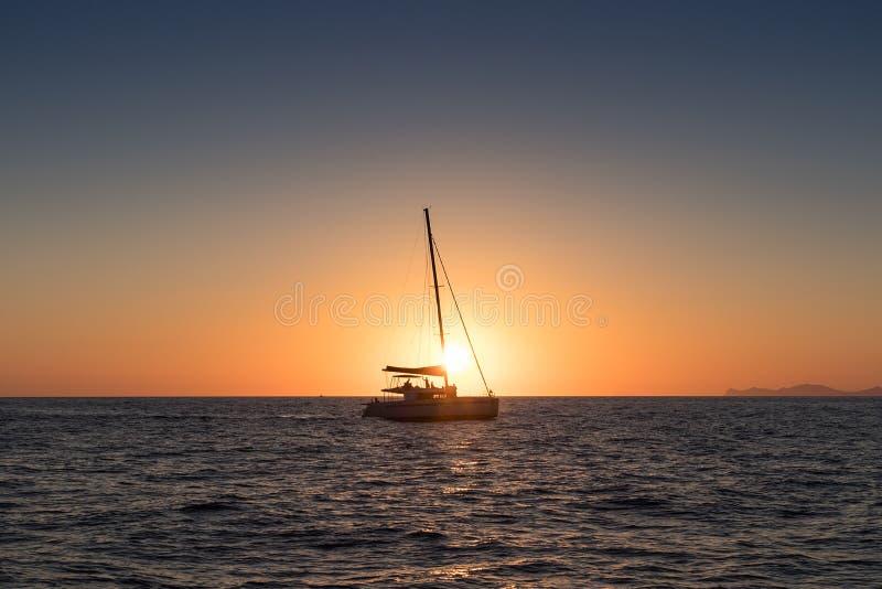 Por do sol bonito em Oia, Santorini, visto do mar com silho imagem de stock royalty free