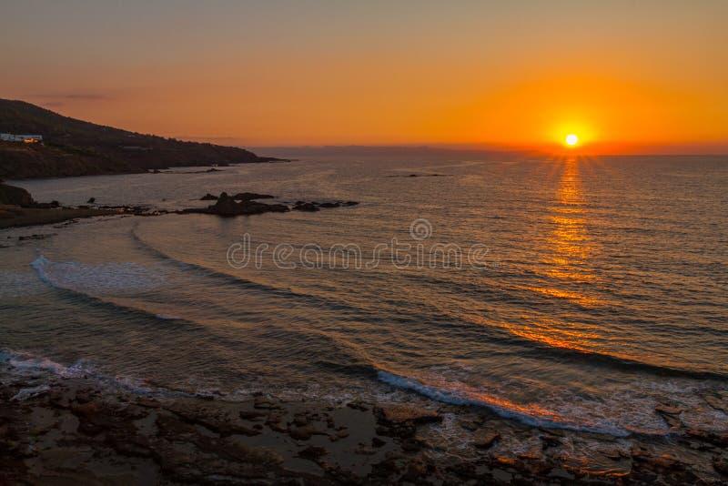 Por do sol bonito em uma praia rochosa em Pomos, Chipre fotografia de stock royalty free