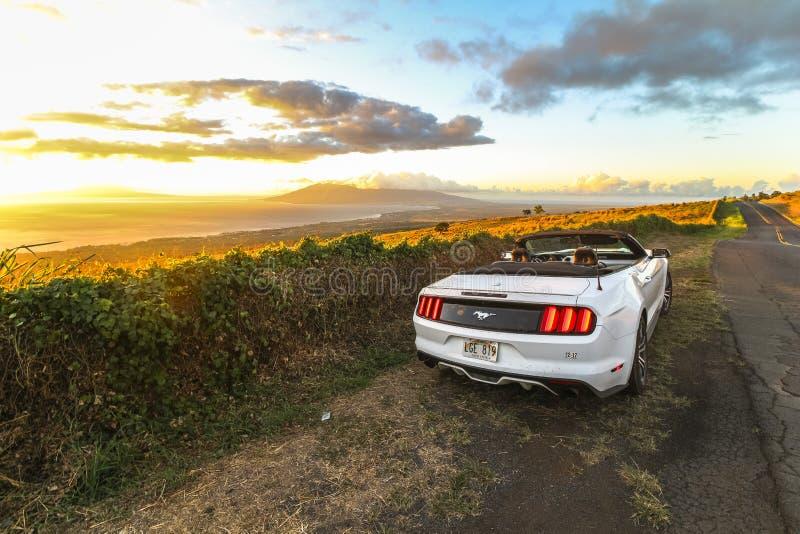 Por do sol bonito na estrada litoral de Maui com convertible imagem de stock