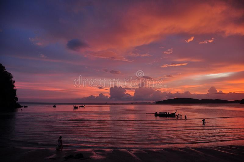 Por do sol bonito na linha costeira, vista pitoresca da praia do Ao Nang com as ondas calmas que correm na costa contra o céu col fotografia de stock royalty free