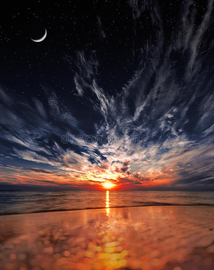 Por do sol bonito na praia, nas estrelas e na lua no céu fotografia de stock