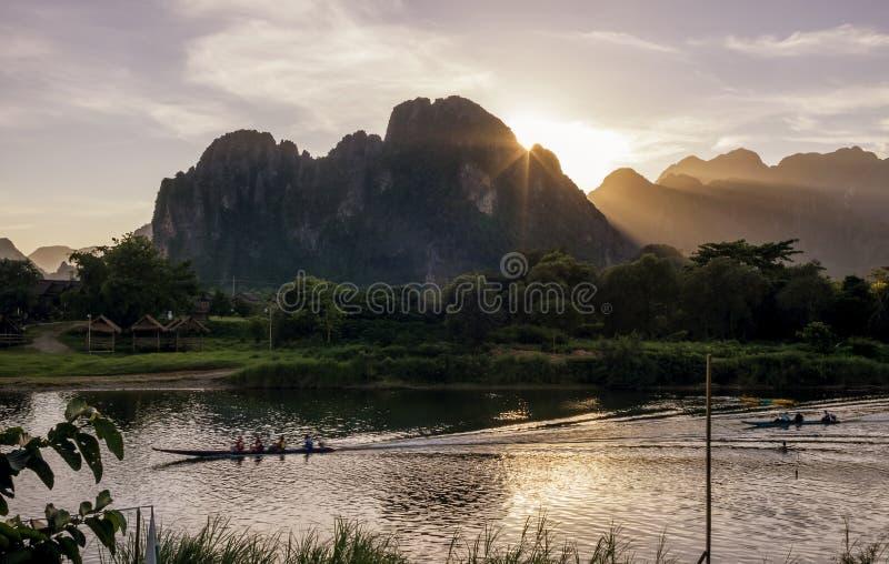 Por do sol bonito no rio de Nam Song em Vang Vieng, Laos, cruzado por barcos de cauda longa imagens de stock royalty free