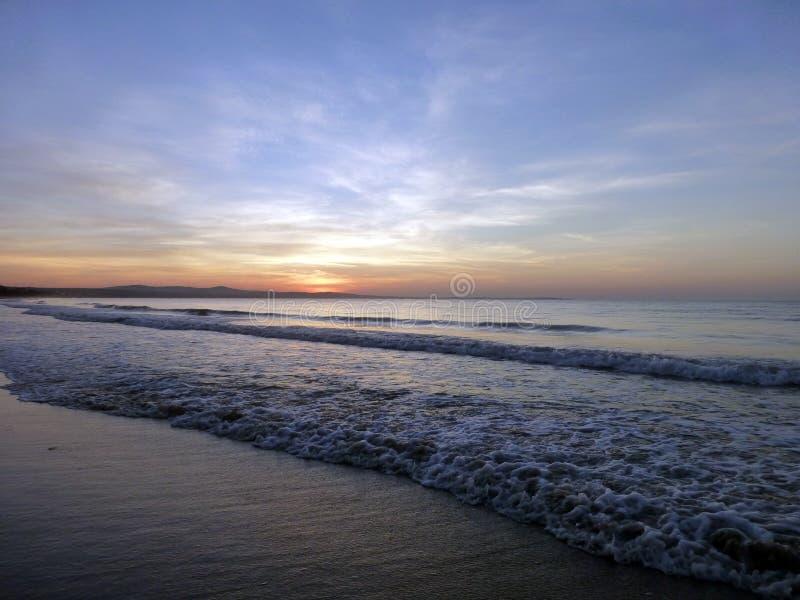 Por do sol bonito os grupos do sol no mar Praia da areia e céu azul com nuvens fotos de stock