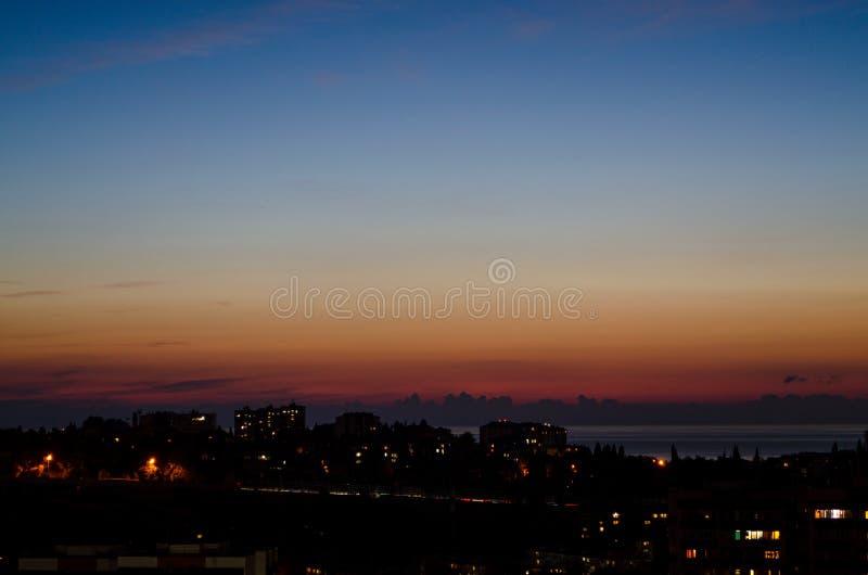 Por do sol bonito sobre a cidade pelo mar imagem de stock