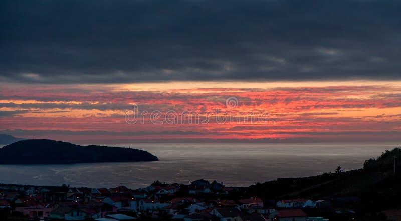 Por do sol bonito sobre a cidade pelo mar fotos de stock royalty free