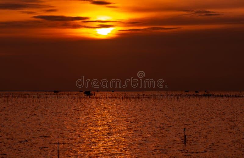 Por do sol bonito sobre o mar Céu e nuvens escuros e dourados do por do sol Fundo da natureza para o conceito tranquilo e calmo P fotos de stock
