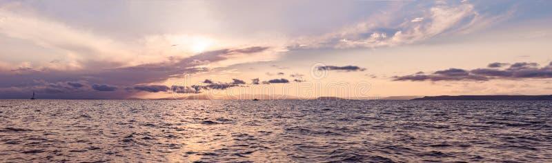 Por do sol bonito sobre o mar com reflexão na água, nuvens majestosas no céu BANDEIRA, formato longo foto de stock