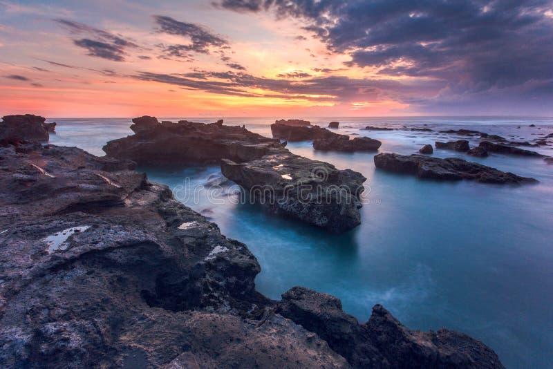 Por do sol bonito sobre o mar rochoso da praia de Mengening imagem de stock
