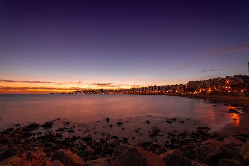 Por do sol bonito sobre o passeio à beira mar e a praia de Montevideo, Uruguai imagens de stock