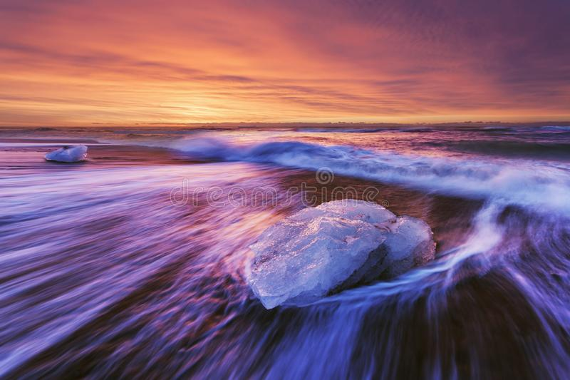 Por do sol bonito sobre a praia famosa do diamante, Islândia Esta praia da lava da areia está completa de muitas gemas gigantes d foto de stock royalty free