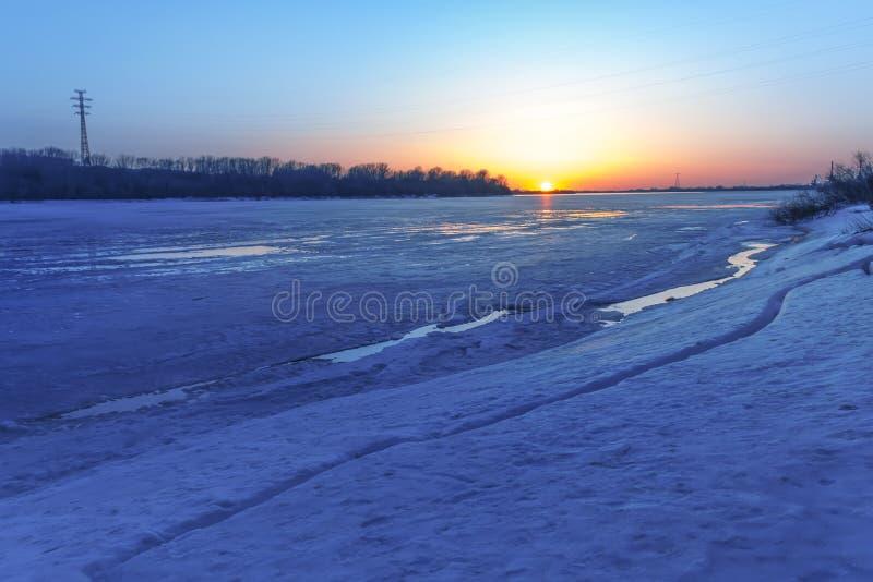 Por do sol bonito sobre um rio congelado O rio é limitado pelo gelo Paisagem da mola foto de stock
