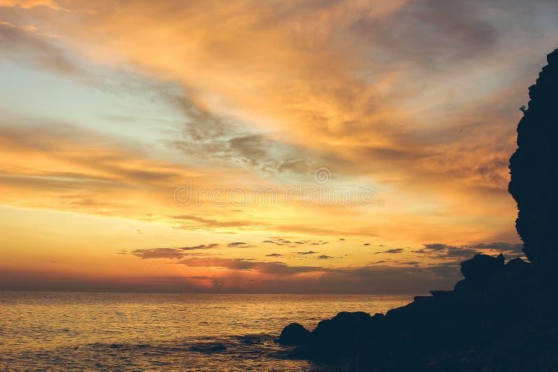 Por do sol bonito surpreendente no litoral perto das rochas com céu dramático imagem de stock