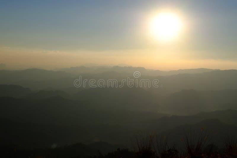 Por do sol borrado na montanha e na névoa superiores na noite foto de stock royalty free