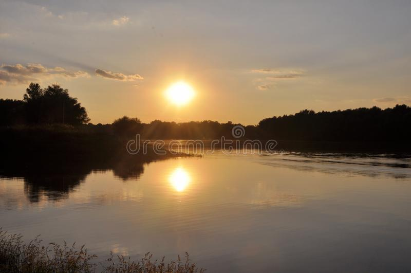 Por do sol brilhante e colorido no rio O sol esconde atrás das árvores na noite Brilho do sol de ajuste na água foto de stock royalty free