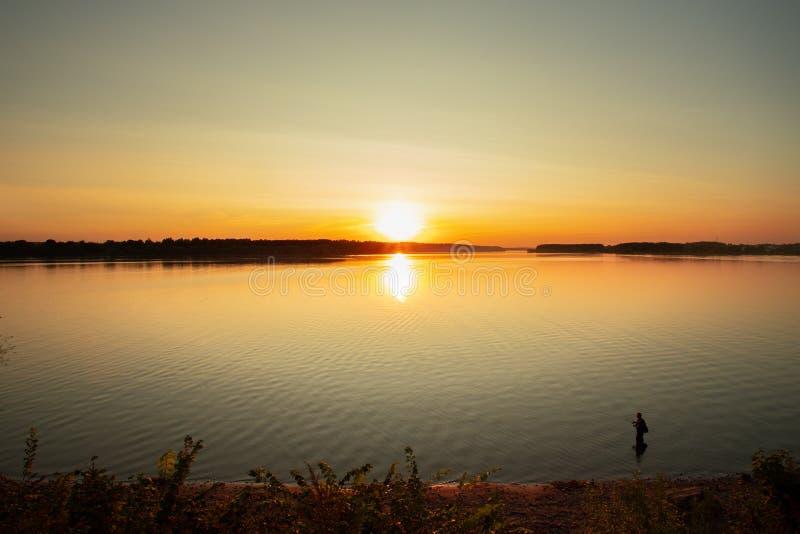 Por do sol brilhantemente colorido Sun atrás de Forest Over River With Fishe imagens de stock