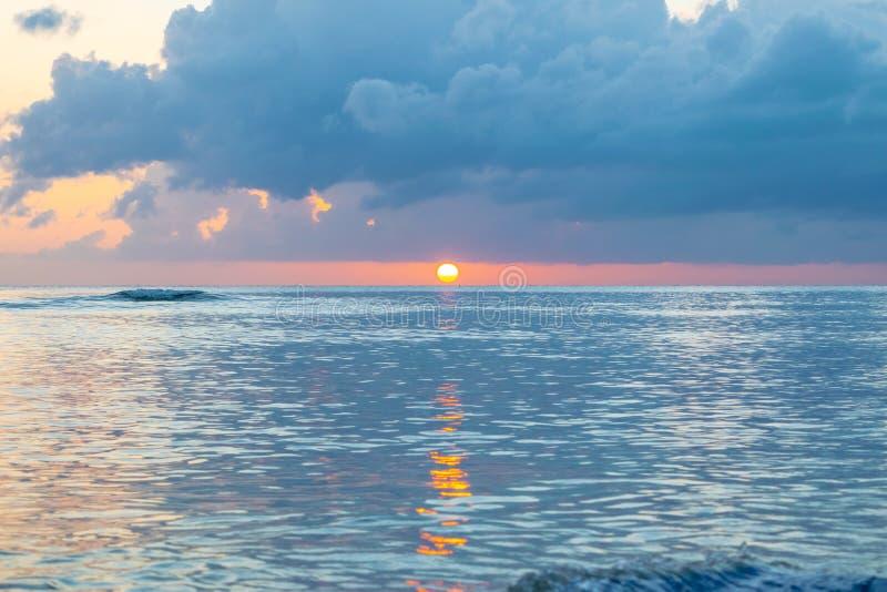 Por do sol c?nico fora da costa da ilha das Cara?bas tropical Sun apenas acima do horizonte foto de stock royalty free