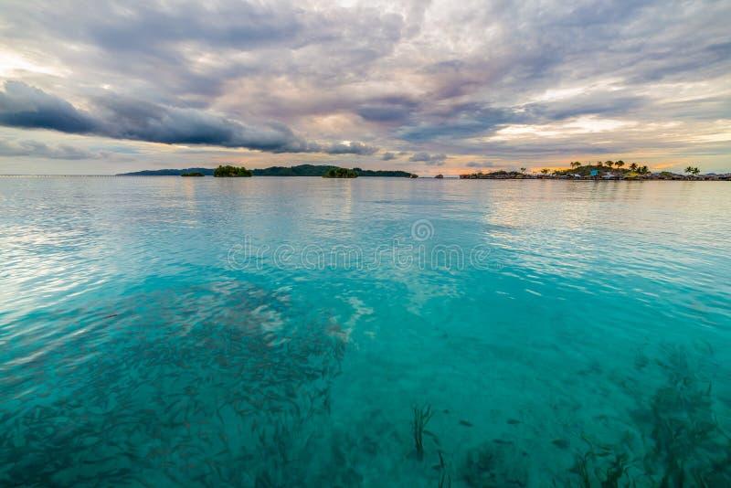 Por do sol cênico no mar transparente, ilhas de Togian, Indonésia fotos de stock royalty free