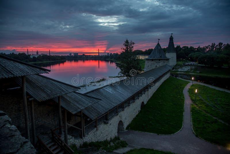 Por do sol carmesim acima das torres do relógio da fortaleza de Pskov fotografia de stock