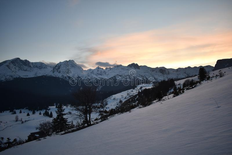 Por do sol coberto de neve da montanha de Durmitor com o c?u de cora imagens de stock