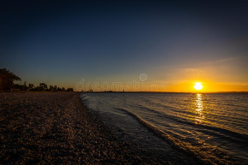 Por do sol colorido bonito sobre a praia do lago Neusiedler em Podersdorf imagens de stock royalty free