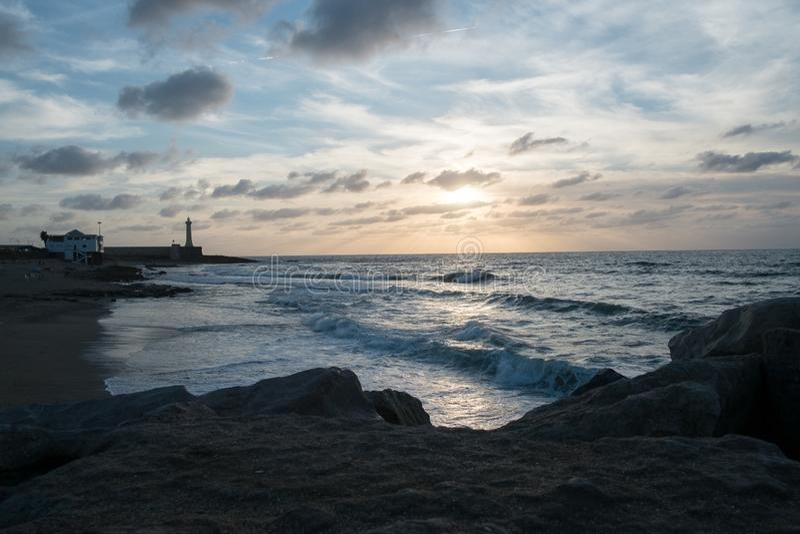 Por do sol colorido em uma baía calma do oceano com um farol e em pedras no primeiro plano imagens de stock royalty free