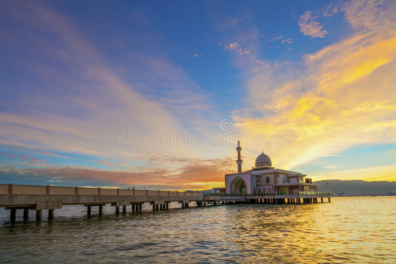Por do sol colorido em uma mesquita de flutuação pelo mar foto de stock