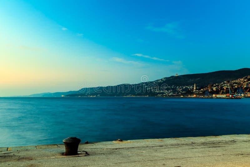 Por do sol colorido na frente da cidade de Trieste imagem de stock royalty free
