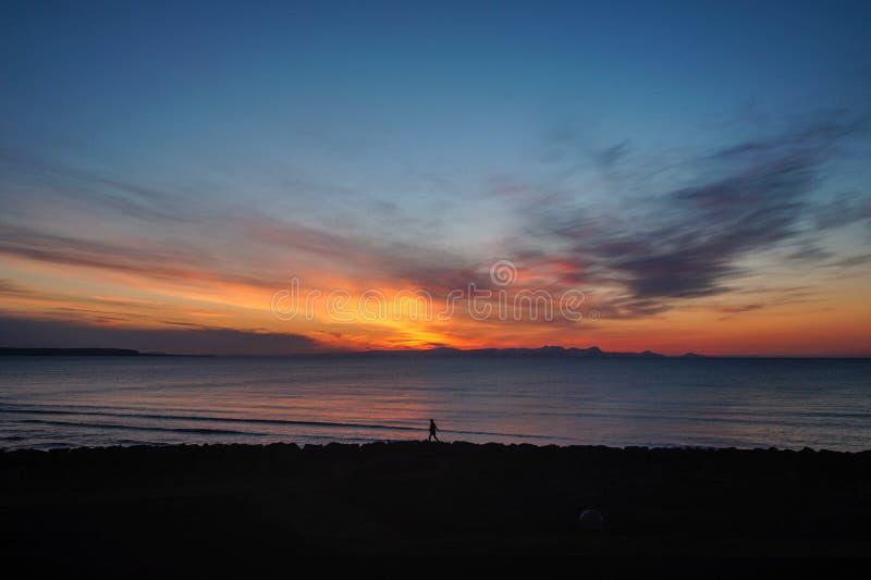 Por do sol colorido na praia de Islândia norte imagem de stock