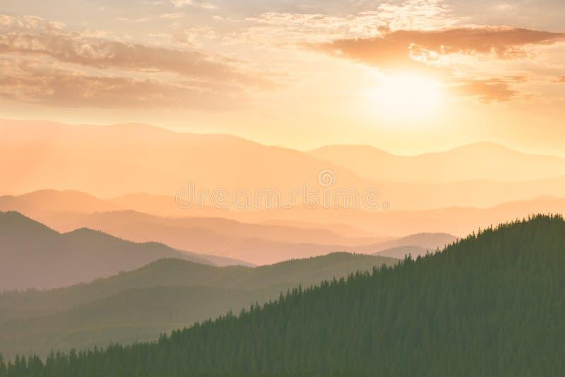 Por do sol colorido nas montanhas, nos montes, no sol e no céu foto de stock royalty free