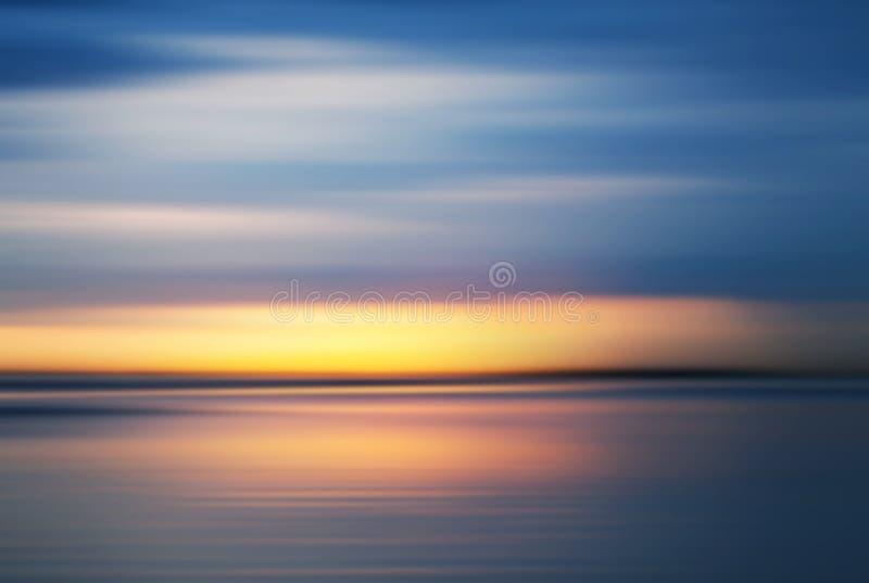 Por do sol colorido sobre a costa de mar sob o céu azul fotografia de stock royalty free