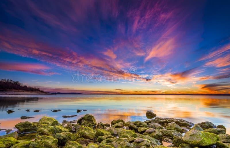 Por do sol colorido sobre o lago imagem de stock