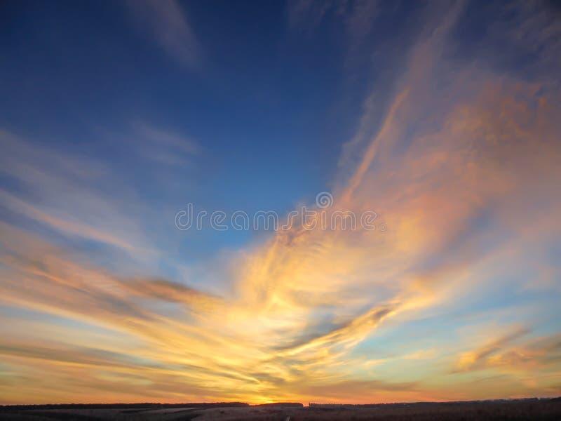 Por do sol com as nuvens cor-de-rosa amarelas no céu azul imagens de stock royalty free