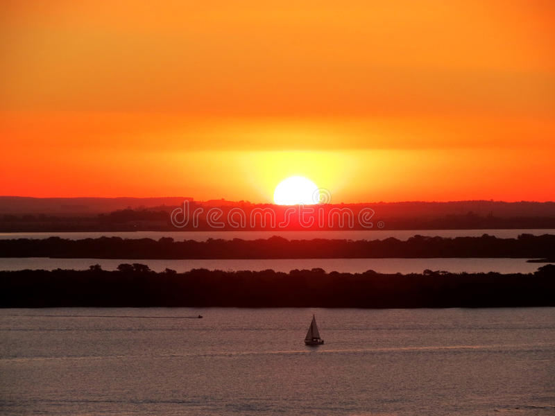 Por do sol com céu amarelo e barco veleiro na água. Sunset evening on the sea river pond with large orange and yellow sunset sky and lots of nature forest royalty free stock photos
