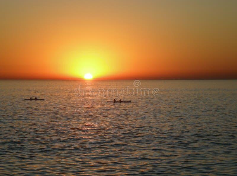 Por do sol com canoas foto de stock