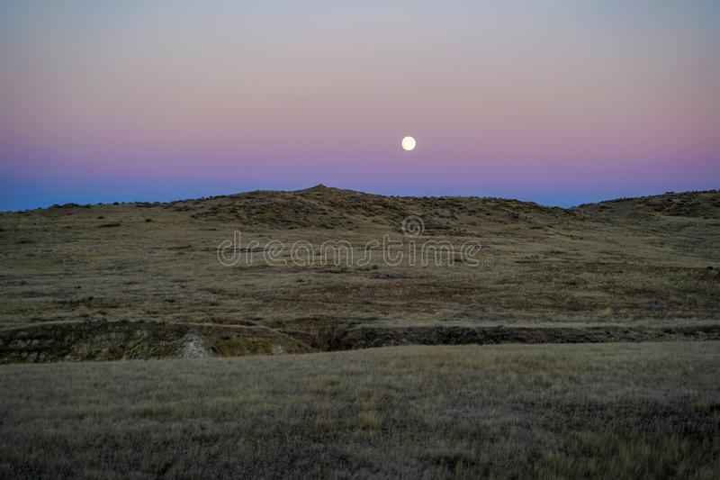 Por do sol com lua e moonrise nas planícies altas do deserto fotografia de stock royalty free