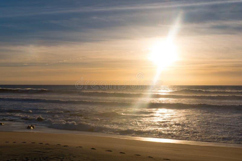 Por do sol com o alargamento da lente na praia com reflexões na água fotos de stock