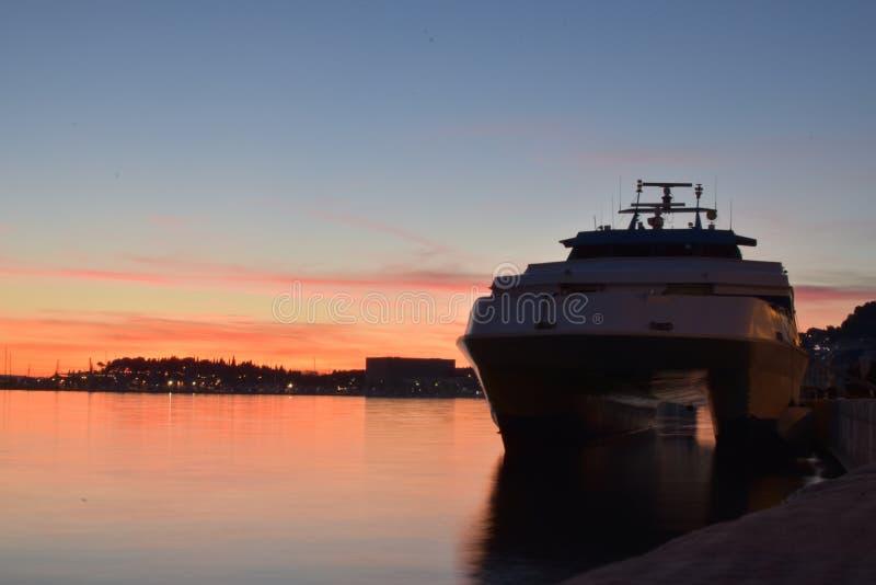 Por do sol com o barco de espera para entregar passangers imagens de stock