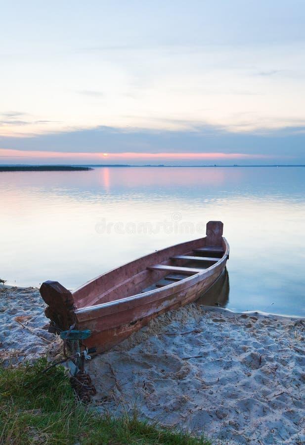 Por do sol com o barco perto da costa do lago do verão imagem de stock