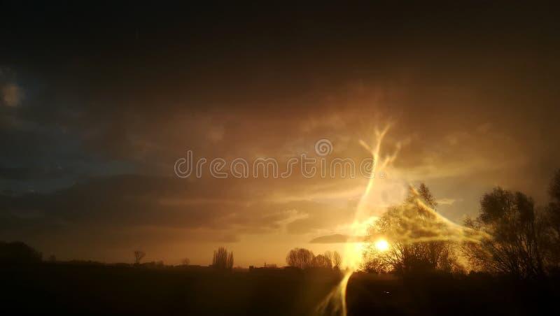 Por do sol com o efeito da luz distorcido causado pela gota da água na lente imagens de stock