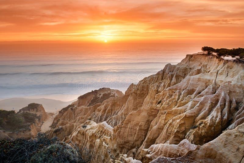 Por do sol com os penhascos da areia na costa de Portugal fotografia de stock royalty free