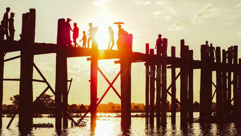 Por do sol com a silhueta dos povos que andam na ponte U-Bein imagens de stock