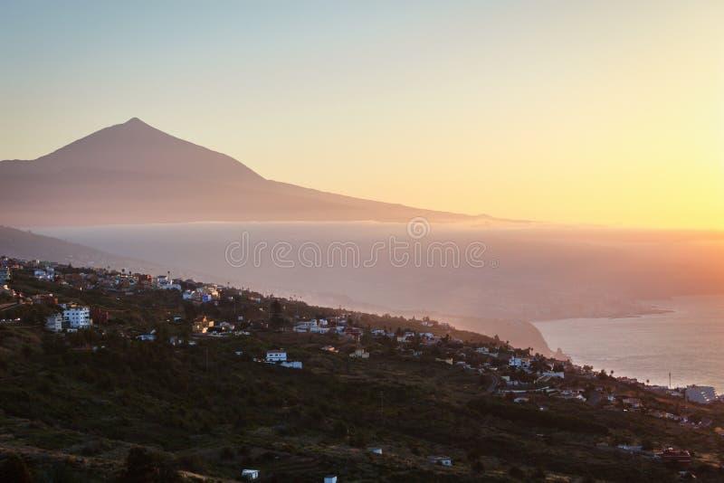 Por do sol com a silhueta do vulcão Teide no fundo, acima das nuvens, abaixo das nuvens a cidade de Santa Cruz, Tenerife fotografia de stock