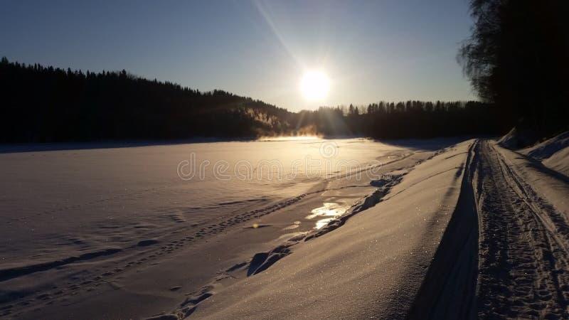 Por do sol congelado do rio e do inverno fotos de stock royalty free